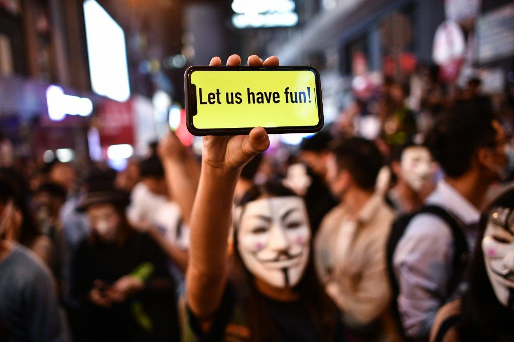 A person displays a message on a mobile phone in front of a line of policemen in the Lan Kwai Fong are...</p>                     </div>                     <div class=