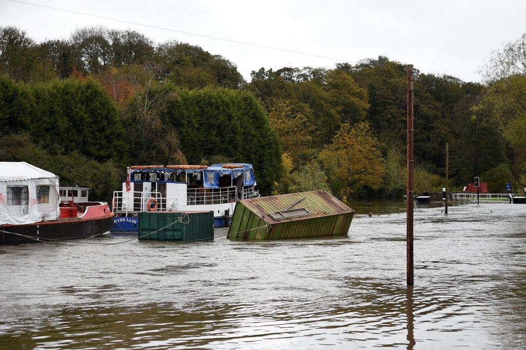 A container floats on the River Don which burst its banks near Doncaster, northern England on November 8, 2019, following flash flooding yesterday. - Over a month's worth of rain fell on parts of England Thursday, with some people forced to evacuate their homes, and others left stranded in a Sheffield shopping centre. (Photo by Oli SCARFF / AFP)