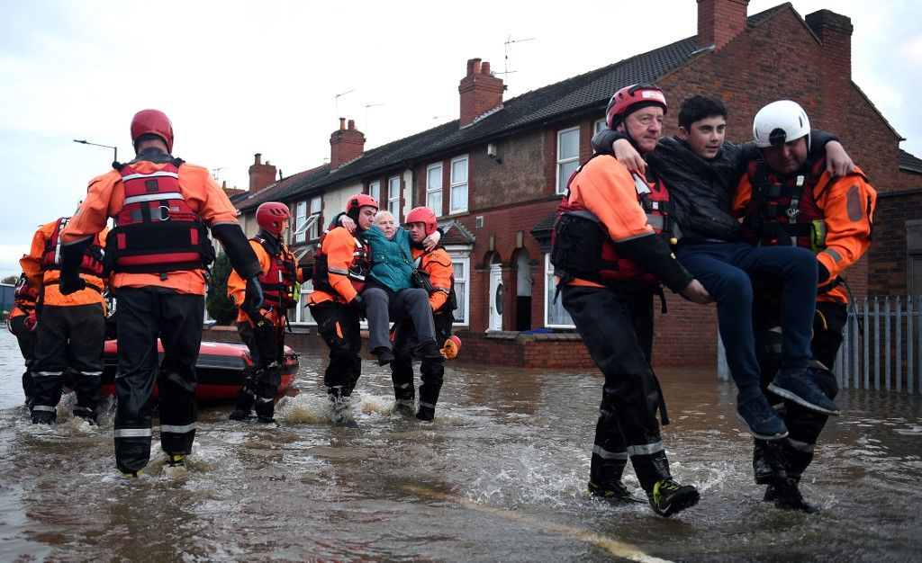 Members of the Fire and Rescue service evacuate residents to dry land, from a flooded house in the Bentley suburb of Doncaster, northern England on November 8, 2019, following flash flooding the previous day. - Over a month's worth of rain fell on parts of England Thursday, with some people forced to evacuate their homes, and others left stranded in a Sheffield shopping centre. (Photo by Oli SCARFF / AFP)