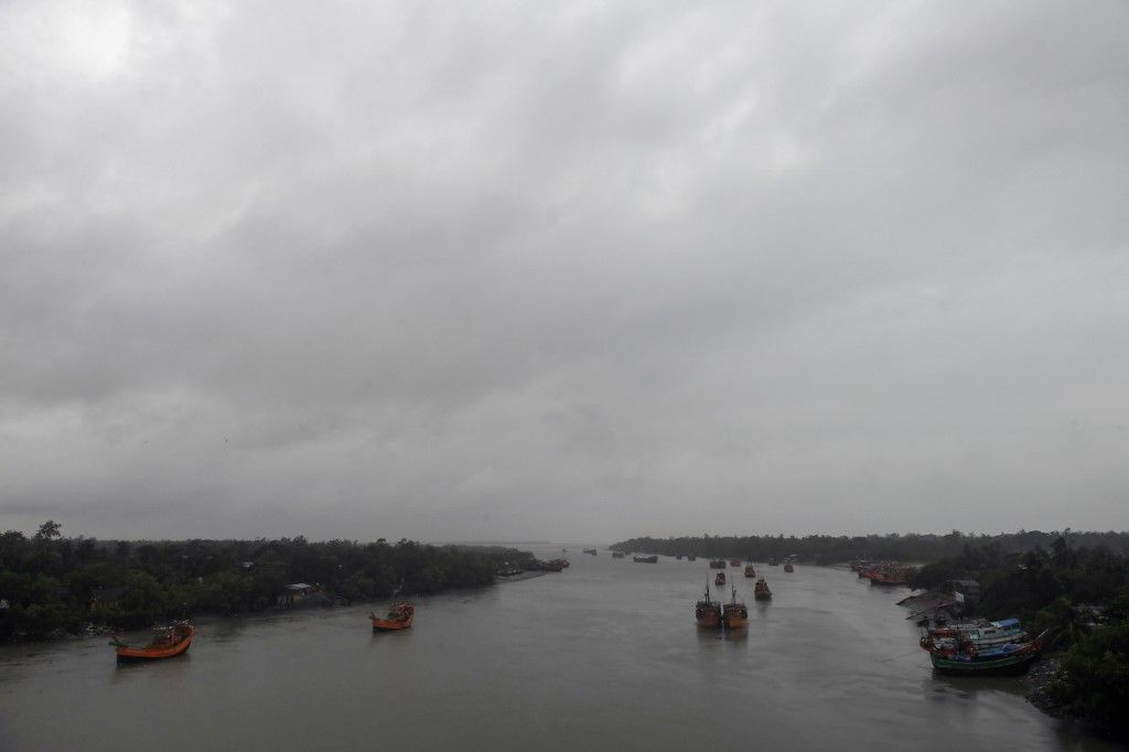 Trawlers return to a fishing harbour under storm clouds from the approaching Cyclone Bulbul in Namkhana in West Bengal state on November 9, 2019. - Cyclone Bulbul, packing a maximum wind speed of 120 kilometres per hour (75 miles), is on course to make landfall near the Sundarbans, the world's largest mangrove forest, which straddles Bangladesh and part of eastern India. (Photo by Dibyangshu SARKAR / AFP)
