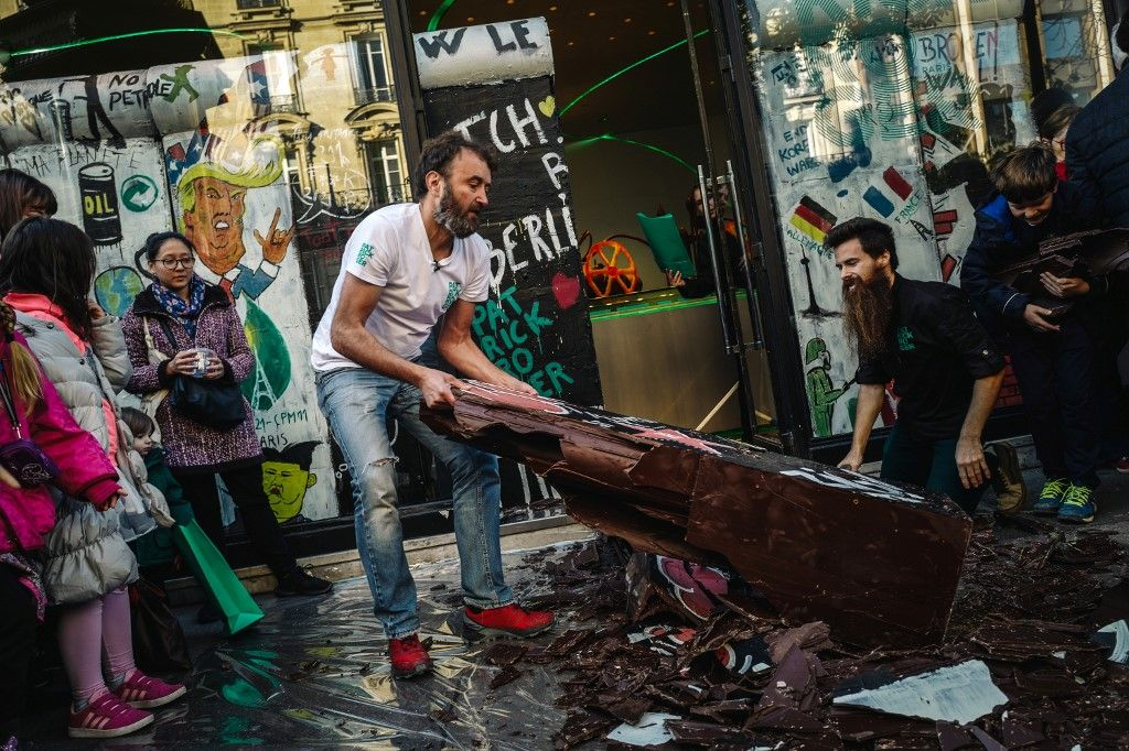 French chocolate maker Patrick Roger (L) and one of his employee break a wall he made with chocolate to commemorate the 30th anniversary of the fall of the Berlin wall on November 9, 2019 in Paris. (Photo by LUCAS BARIOULET / AFP)