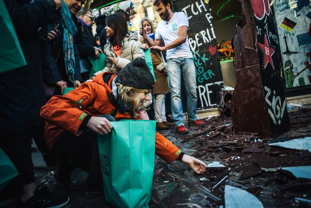 People collect pieces of a wall made with chocolate by French chocolate maker Patrick Roger (background) to commemorate the 30th anniversary of the fall of the Berlin wall on November 9, 2019 in Paris. (Photo by LUCAS BARIOULET / AFP)