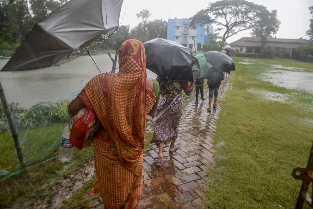 Villagers holding umbrellas carry their belongings on their way to enter a relief centre as Cyclone Bulbul is approaching, in Bakkhali near Namkhana in Indian state of West Bengal on November 9, 2019. - Cyclone Bulbul, packing a maximum wind speed of 120 kilometres per hour (75 miles), is on course to make landfall near the Sundarbans, the world's largest mangrove forest, which straddles Bangladesh and part of eastern India. (Photo by Dibyangshu SARKAR / AFP)