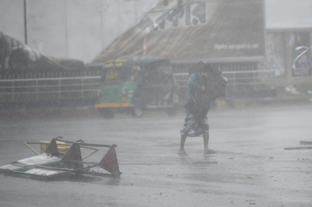 A pedestrian makes his way under heavy rain as Cyclone Bulbul approaches the area in Khulna on November 10, 2019. - Cyclone Bulbul hit India and southern Bangladesh on November 09, leaving at least three dead as authorities in the countries ordered more than two million people to get out of the path of the storm. (Photo by Munir UZ ZAMAN / AFP)