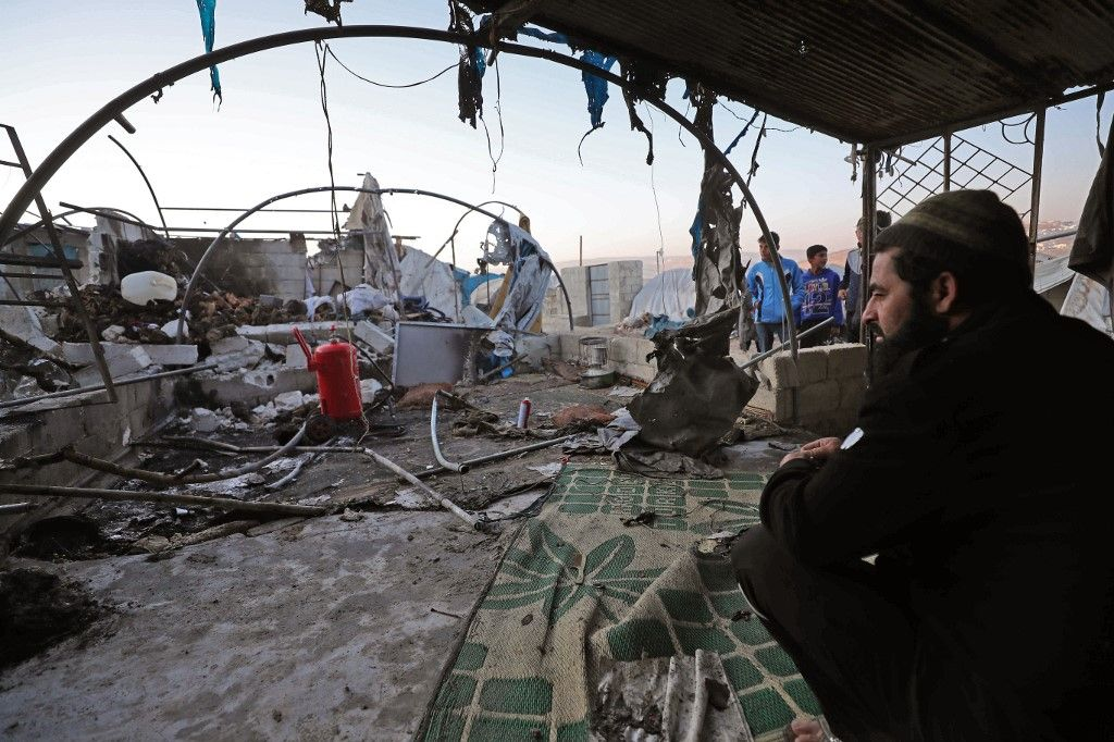 A man sits inside a damaged tent following Syrian regime bombardment on a makeshift camp in the village of Qah near the Turkish border in the northwestern Idlib province on November 21, 2019. - The Syrian Observatory for Human Rights, in an updated toll, said a ground-to-ground missile fired by regime forces that hit a makeshift camp for the displaced near Qah village close to the border with Turkey killed 15 civilians, including six children, and wounded around 40 others. The missile crashed near a maternity facility in the camp, it said.