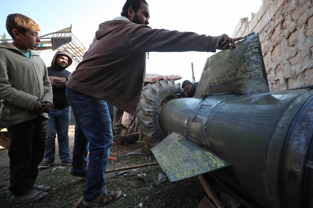 A man touches a fragment of a ground-to-ground missile fired by Syrian regime forces and hit a makeshift camp in the village of Qah near the Turkish border in the northwestern Idlib province on November 21, 2019. - The Syrian Observatory for Human Rights, in an updated toll, said a ground-to-ground missile fired by regime forces that hit a makeshift camp for the displaced near Qah village close to the border with Turkey killed 15 civilians, including six children, and wounded around 40 others. The missile crashed near a maternity facility in the camp, it said.