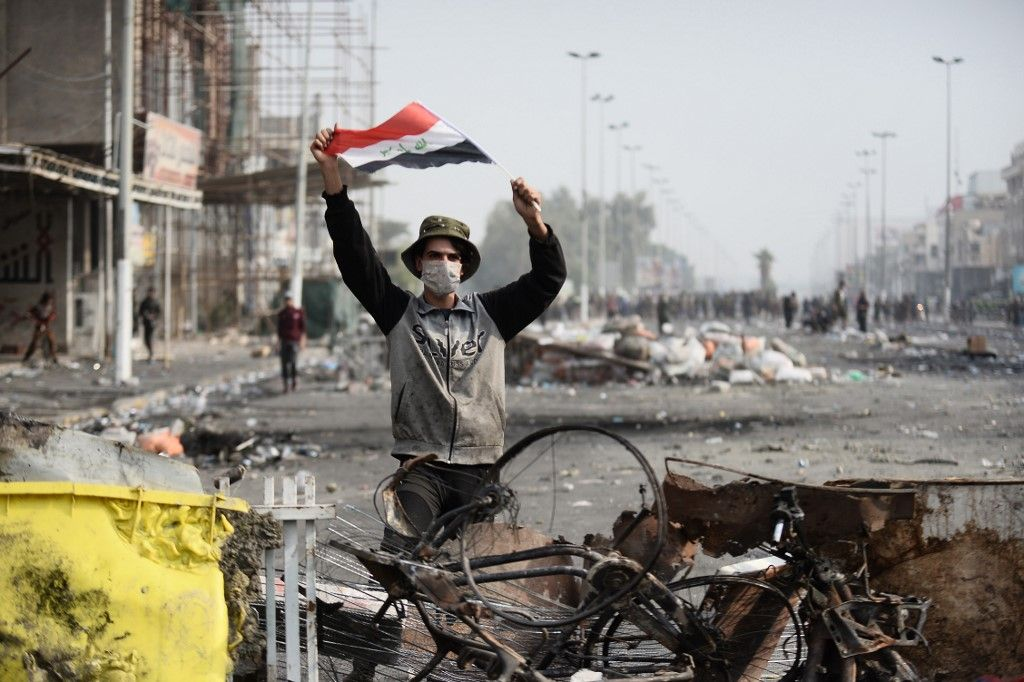 An Iraqi demonstrator carries the national flag in the southern Iraqi Shiite holy city of Najaf on December 1, 2019. - Protesters have hit the streets since early October in the largest grassroots movement Iraq has seen in decades, sparked by fury at poor public services, lack of jobs and widespread government graft. Security forces and armed groups responded with violence to demonstrations, killing more than 420 people and wounding 15,000, according to an AFP tally compiled from medics and an Iraqi rights commission.