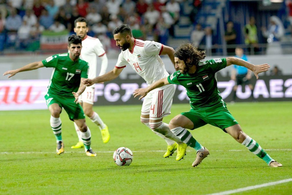 DUBAI, UNITED ARAB EMIRATES - JANUARY 16: Saman Ghoddos of Iran holds off Hussein Al-Saedi of Iranduring the AFC Asian Cup Group D match between Iran and Iraq at Al Maktoum Stadium on January 16, 2019 in Dubai, United Arab Emirates.