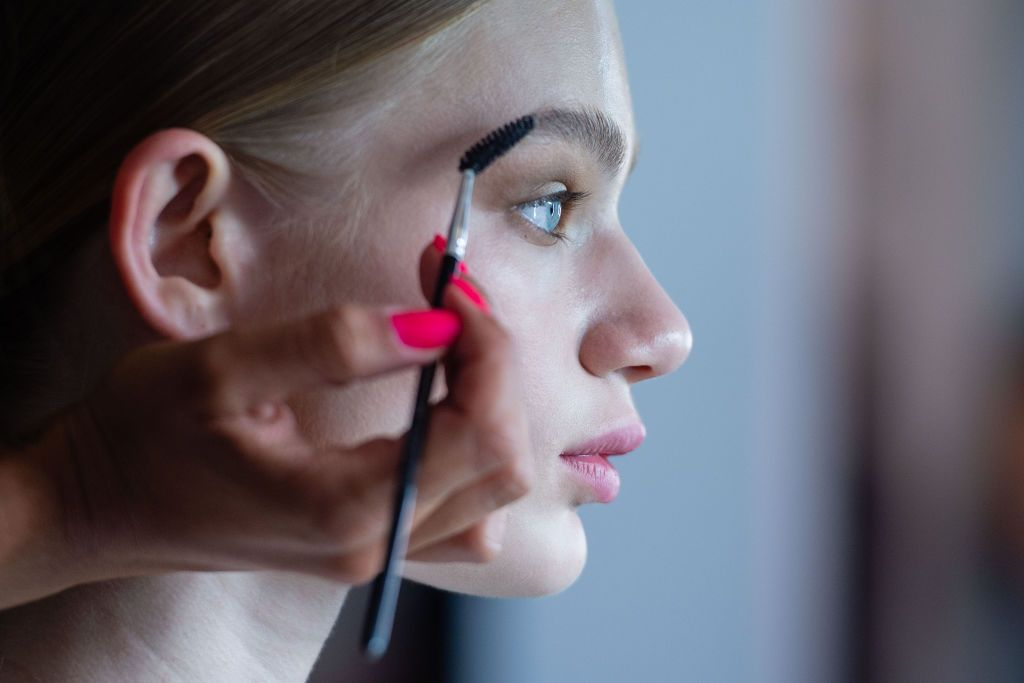 03 July 2019, Berlin: A make-up stylist takes care of the eyebrows of a model for the show of designer Marcel Ostertag. The collections for Spring/Summer 2020 will be presented at Berlin Fashion Week. Photo: Lisa Ducret/dpa (Photo by Lisa Ducret/picture alliance via Getty Images)