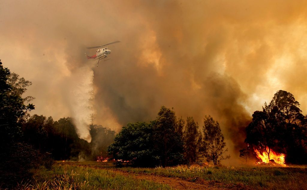 A fire bombing helicopter works to contain a bushfire along Old Bar road in Old Bar, New South Wales, Australia, November 9, 2019. AAP Image/Shane Chalker/via REUTERS  ATTENTION EDITORS - THIS IMAGE WAS PROVIDED BY A THIRD PARTY. NO RESALES. NO ARCHIVE. AUSTRALIA OUT. NEW ZEALAND OUT.
