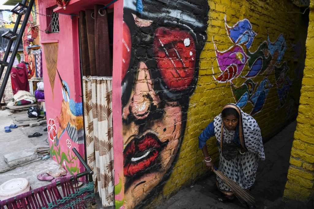 A woman sweeps an alleyway adorned with murals painted by artists from 'Delhi Street Art' group at the Raghubir Nagar slum in New Delhi on December 2, 2019. - A New Delhi slum has been given a colourful makeover thanks to a street artist collective, drawing art lovers and selfie-snappers to a rundown area that they would never normally visit. (Photo by Sajjad HUSSAIN / AFP) / RESTRICTED TO EDITORIAL USE - MANDATORY MENTION OF THE ARTIST UPON PUBLICATION - TO ILLUSTRATE THE EVENT AS SPECIFIED IN THE CAPTION
