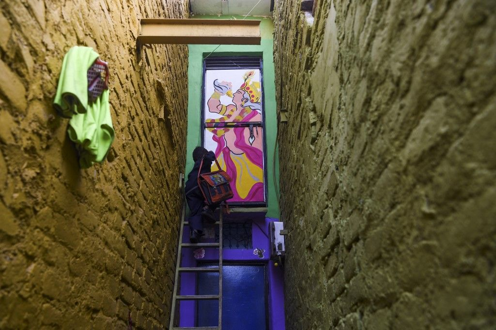 A boy climbs up a ladder to enter a home adorned with a mural painted by artists from 'Delhi Street Art' group at the Raghubir Nagar slum in New Delhi on December 2, 2019. - A New Delhi slum has been given a colourful makeover thanks to a street artist collective, drawing art lovers and selfie-snappers to a rundown area that they would never normally visit. (Photo by Sajjad HUSSAIN / AFP) / RESTRICTED TO EDITORIAL USE - MANDATORY MENTION OF THE ARTIST UPON PUBLICATION - TO ILLUSTRATE THE EVENT AS SPECIFIED IN THE CAPTION