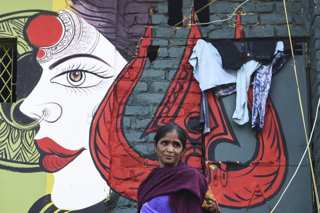 A woman leaves her home adorned with a mural painted by artists from 'Delhi Street Art' group at the Raghubir Nagar slum in New Delhi on December 2, 2019. - A New Delhi slum has been given a colourful makeover thanks to a street artist collective, drawing art lovers and selfie-snappers to a rundown area that they would never normally visit. (Photo by Sajjad HUSSAIN / AFP) / RESTRICTED TO EDITORIAL USE - MANDATORY MENTION OF THE ARTIST UPON PUBLICATION - TO ILLUSTRATE THE EVENT AS SPECIFIED IN THE CAPTION