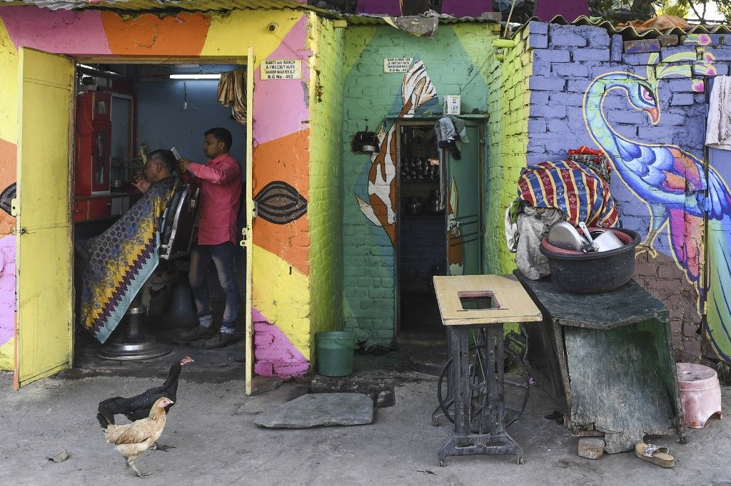 A barber tends to a customer in his shop adorned with murals painted by artists from 'Delhi Street Art' group at the Raghubir Nagar slum in New Delhi on December 2, 2019. - A New Delhi slum has been given a colourful makeover thanks to a street artist collective, drawing art lovers and selfie-snappers to a rundown area that they would never normally visit. (Photo by Sajjad HUSSAIN / AFP) / RESTRICTED TO EDITORIAL USE - MANDATORY MENTION OF THE ARTIST UPON PUBLICATION - TO ILLUSTRATE THE EVENT AS SPECIFIED IN THE CAPTION