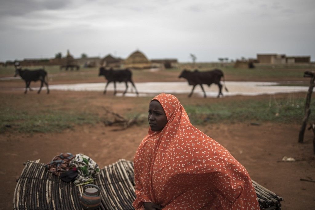 Safira, a nomadic Fulani woman sits on a straw mat outside her family hut in a Fulani camp in Dosso, on June 22, 2019. - Higher temperatures, shifting winds and moisture levels that alter rainfall patterns, sandstorms, torrential rain -- all can change the quality or even the location of pasture on which migrating herders depend. This year, for the Fulani, has been relatively good. The herdsman were able to draw on stocks of animal feed to help them survive stress points, while timely rainfall on some areas of the migration trail helped tender young grass to grow. But whether this respite endures is the big question. (Photo by Marco LONGARI / AFP)