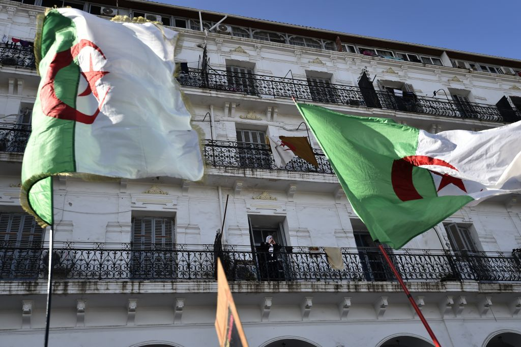 Algerians wave a national flags during an march in the capital Algiers o...</p>                     </div>                     <div class=