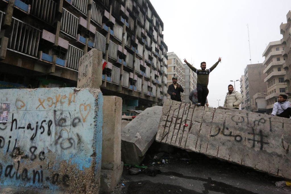 An Iraqi protester gestures as he stands on a cement block at Al-Khilani square in the capital Baghdad amid ongoing anti-government demonstrations, on December 7, 2019. - An armed drone targeted the home of Iraqi cleric Moqtada Sadr today, hours after his supporters deployed in Baghdad in response to an attack that left 17 protesters dead. The developments marked a worrying turn for the anti-government demonstrations rocking Iraq since October, the country's largest and deadliest grassroots movement in decades. (