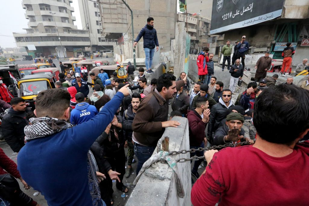 Iraqi protesters move a cement block at Al-Khilani square in the capital Baghdad amid ongoing anti-government demonstrations, on December 7, 2019. - An armed drone targeted the home of Iraqi cleric Moqtada Sadr today, hours after his supporters deployed in Baghdad in response to an attack that left 17 protesters dead. The developments marked a worrying turn for the anti-government protests rocking Iraq since October, the country's largest and deadliest grassroots movement in decades.