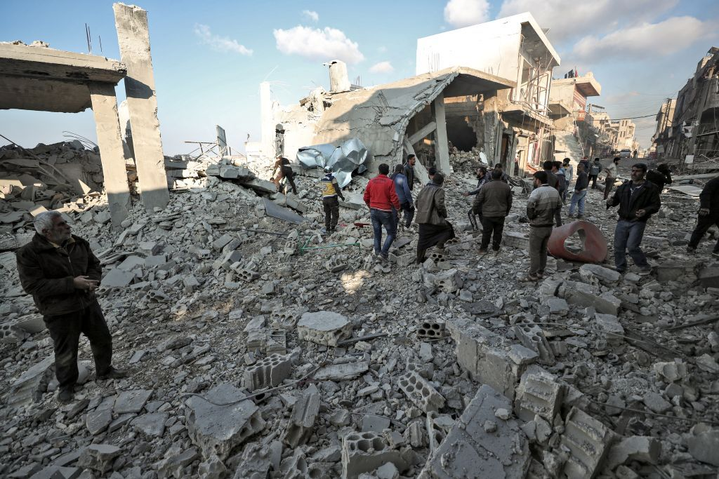 Members of the Syrian Civil Defense known as White Helmets and locals search for victims in the rubble of a building after a reported Russian airstrike on a popular market in the village of Balyun in Syria's northwestern Idlib province, on December 7, 2019. - Syrian regime and Russian air strikes killed 19 civilians today, eight of them children, in Idlib, the country's last major opposition bastion, a war monitor said. (Photo by Omar HAJ KADOUR / AFP)