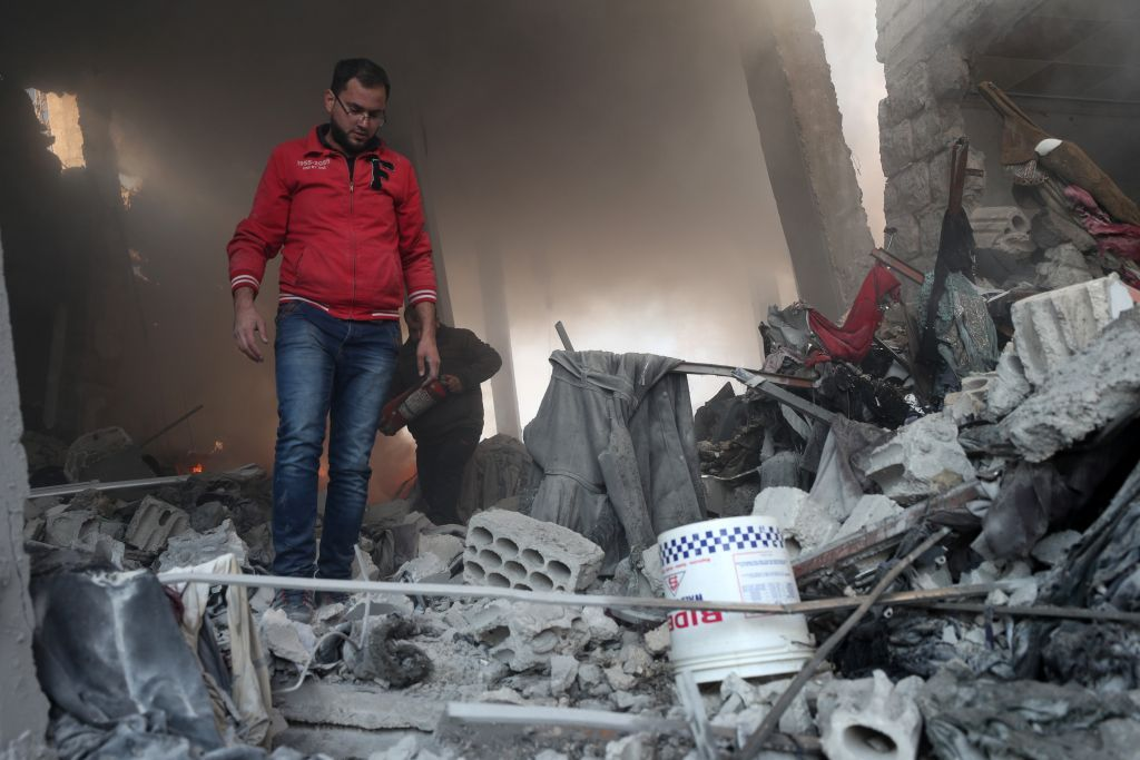 Syrian men search for victims in the rubble of a building still on fire after a reported Russian airstrike on a popular market in the village of Balyun in Syria's northwestern Idlib province, on December 7, 2019. - Syrian regime and Russian air strikes killed 19 civilians today, eight of them children, in Idlib, the country's last major opposition bastion, a war monitor said. (Photo by Omar HAJ KADOUR / AFP)
