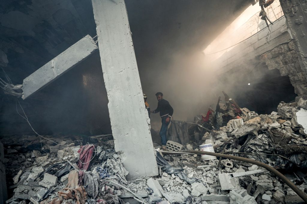 Helmets and locals search for victims in the rubble of a building after a reported Russian airstrike on a popular market in the village of Balyun in Syria's northwestern Idlib province, on December 7, 2019. - Syrian regime and Russian air strikes killed 19 civilians today, eight of them children, in Idlib, the country's last major opposition bastion, a war monitor said. (Photo by Omar HAJ KADOUR / AFP)