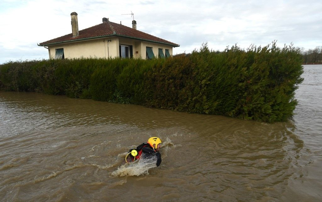 A firefighter swim in a flooded neighbourhood following heavy rains in Peyrehorade, southwestern France, on December 14, 2019. - About 70,000 houses were cut from electricity on December 13, 2019 in southwestern France after heavy rains and violent winds. One person died and five others were injured as the floods threaten the Pyrenees-Atlantiques region. (Photo by GAIZKA IROZ / AFP)