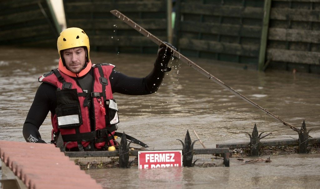 A firefighter inspect a flooded neighbourhood following heavy rains in Peyrehorade, southwestern France, on December 14, 2019. - About 70,000 houses were cut from electricity on December 13, 2019 in southwestern France after heavy rains and violent winds. One person died and five others were injured as the floods threaten the Pyrenees-Atlantiques region. (Photo by Iroz Gaizka / AFP)