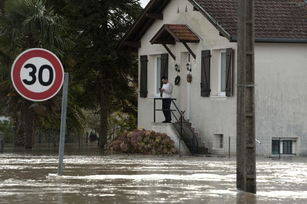 A man stands outside a house in a flooded neighbourhood following heavy rains in Peyrehorade, southwestern France, on December 14, 2019. - About 70,000 houses were cut from electricity on December 13, 2019 in southwestern France after heavy rains and violent winds. One person died and five others were injured as the floods threaten the Pyrenees-Atlantiques region. (Photo by Iroz Gaizka / AFP)