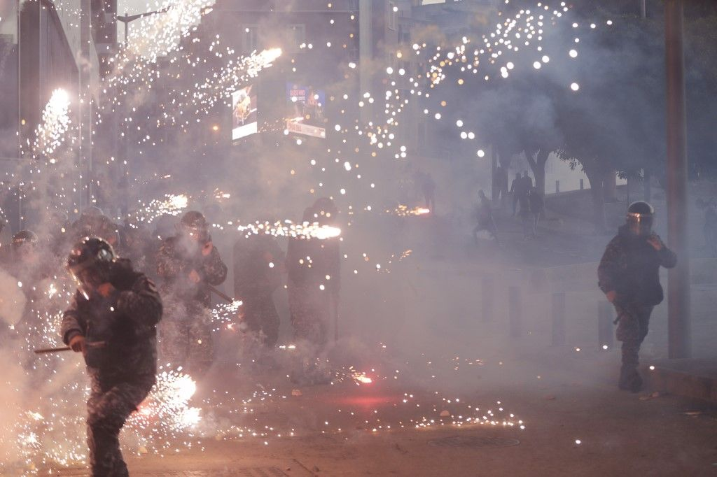 Lebanese riot police react to fireworks thrown by supporters of Lebanon's Shiite Hezbollah and Amal groups during clashes on December 14, 2019 in central Beirut. (Photo by ANWAR AMRO / AFP)