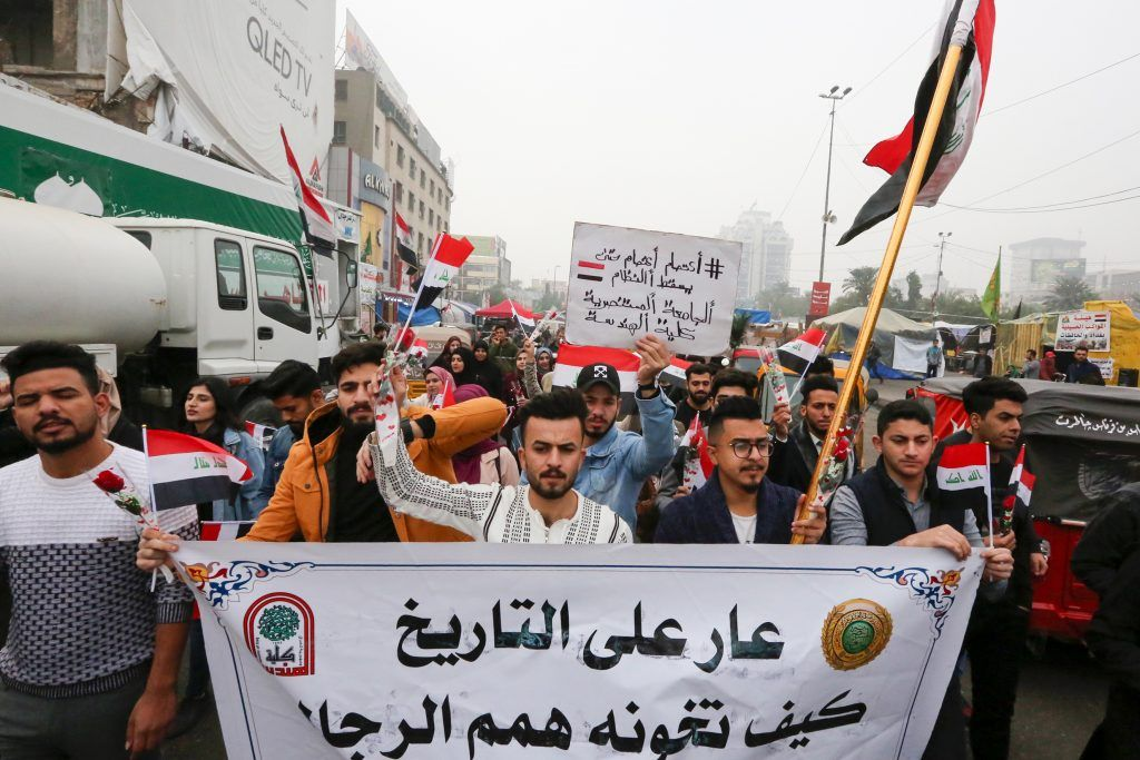 Iraqi protesters march during a anti-government protest in Tahrir square in the capital Baghdad, on December 15, 2019. - Iraq's capital and Shiite-majority south have been gripped Since October 1, by rallies against corruption, poor public services, a lack of jobs and Iran's perceived political interference. (Photo by SABAH ARAR / AFP)