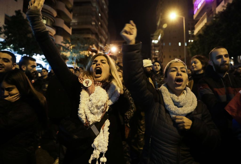 Lebanese protesters shout slogans as they gather outside the house of Lebanon's new prime minister in the capital Beirut, calling for his resignation less than 10 days after he was appointed, on December 28, 2019. - Protests continued after the resignation of the previous prime minister, while political parties negotiated for weeks before nominating Hassan Diab, a professor and former education minister, to replace him on December 19. (Photo by ANWAR AMRO / AFP)