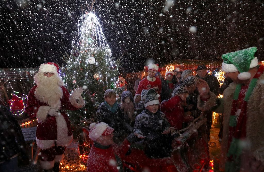 """Serge Hennebel, nicknamed """"Elf Serge"""", and a man dressed as Santa Claus (Father Christmas) interact with children in a hut in Hennebel's garden, which has been transformed into a Christmas village and adorned with hundreds of lights, in Hamme-Mille, Belgium December 7, 2019  REUTERS/Yves Herman"""