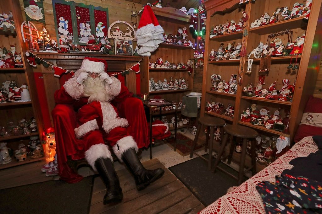 A man dressed as Santa Claus (Father Christmas) sits in a house transformed into a Christmas village and adorned with hundreds of lights, in Hamme-Mille, Belgium December 7, 2019  REUTERS/Yves Herman