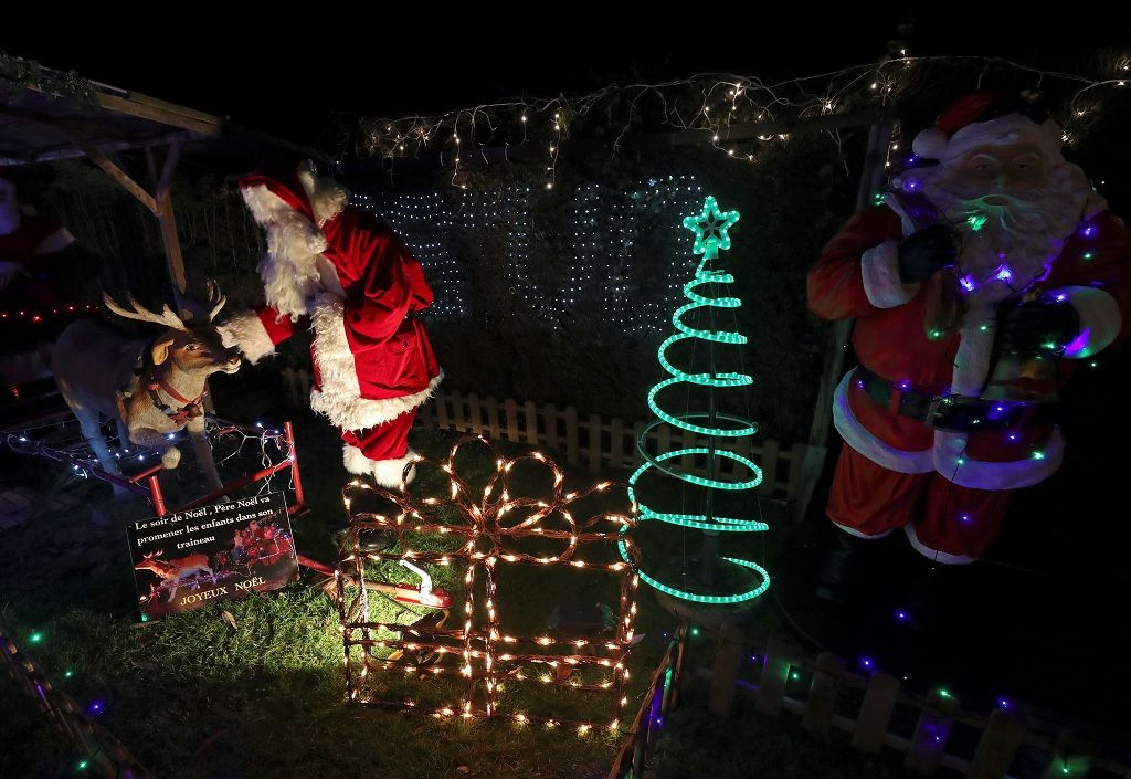 """A man dressed as Santa Claus (Father Christmas) is seen in a garden that belongs to Serge Hennebel, nicknamed """"Elf Serge"""" and has been transformed into a Christmas village adorned with hundreds of lights, in Hamme-Mille, Belgium December 7, 2019  REUTERS/Yves Herman"""