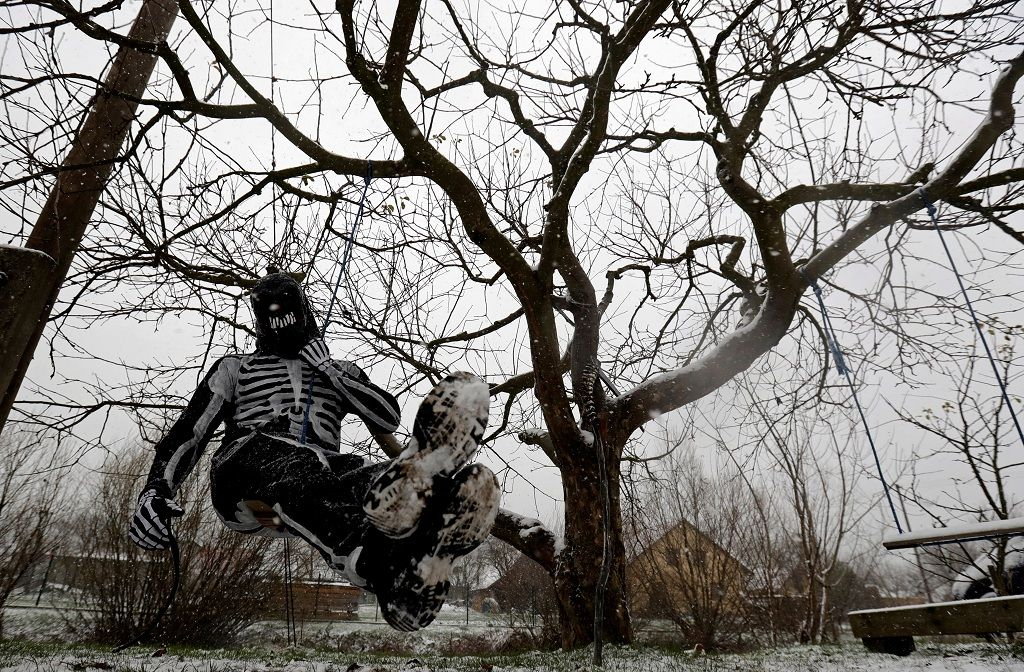 A reveller dressed as devil hangs from a tree in the village of Valasska Polanka during a traditional Saint Nicholas parade near the town of Vsetin, Czech Republic, December 7, 2019. REUTERS/David W Cerny