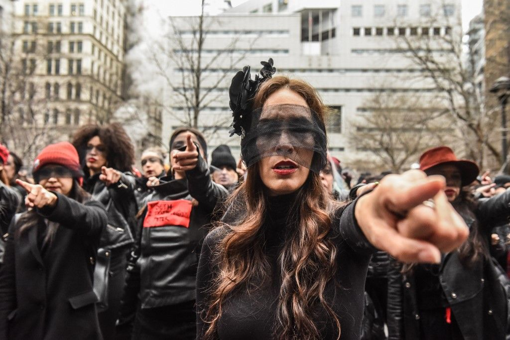 """NEW YORK, NY - JANUARY 10 : Women inspired by the Chilean feminist group called Las Tesis perform """"the rape dance"""" in front of the New York City criminal court during Harvey Weinstein's sex crimes trial on January 10, 2020 in New York City. Weinstein, a movie producer whose alleged sexual misconduct helped spark the #MeToo movement, pleaded not-guilty on five counts of rape and sexual assault against two unnamed women and faces a possible life sentence in prison.   Stephanie Keith/Getty Images/AFP"""