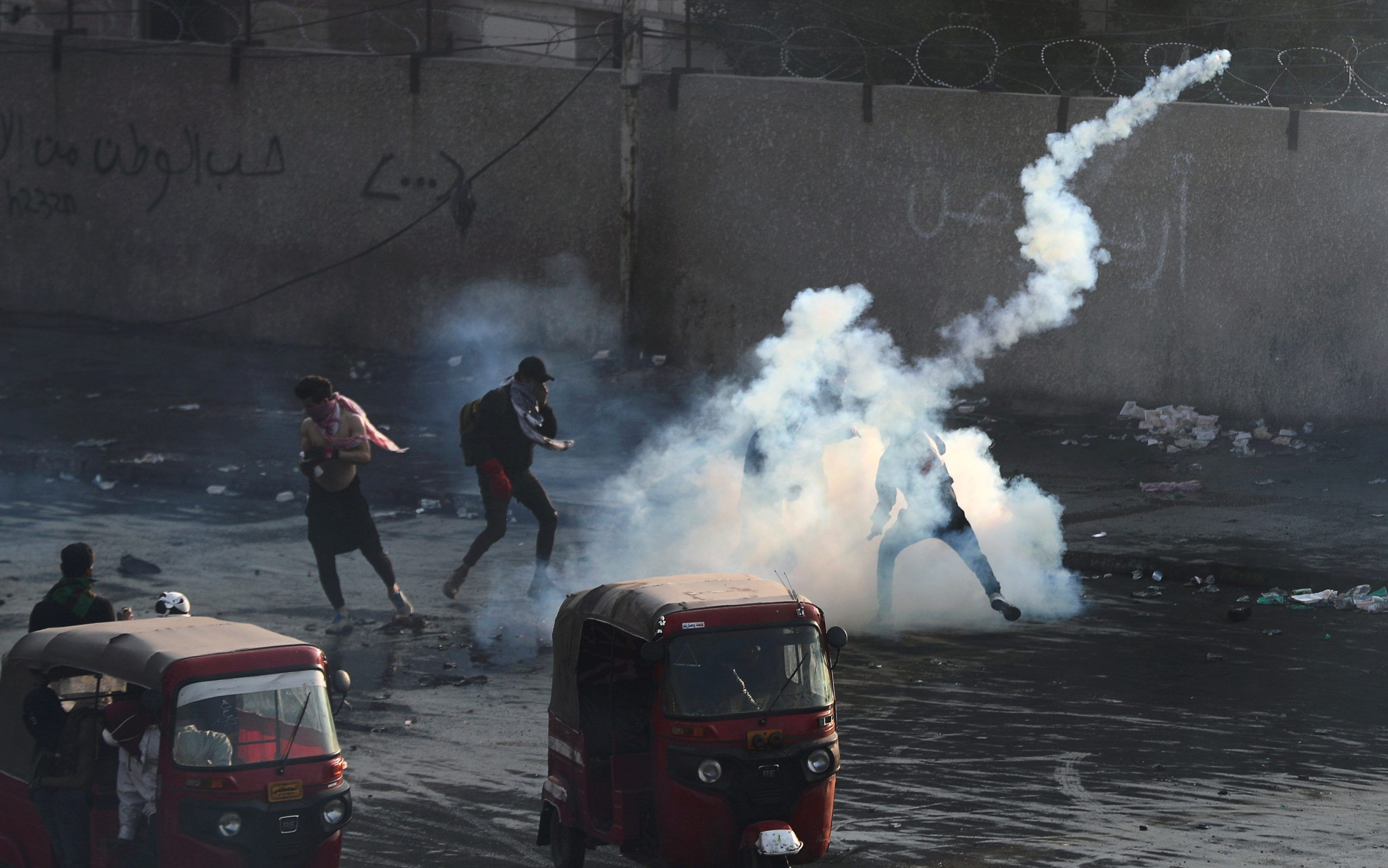 Iraqi demonstrators run from tear gas thrown during ongoing anti-government protests in Baghdad, Iraq January 20, 2020.