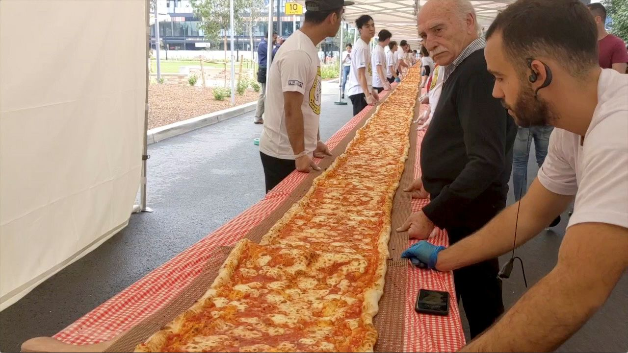 People look at a 100m long margherita pizza before it receives its final toppings, which was prepared by Pellegrini's Italian restaurant in their attempt to set a new record for Australia's longest pizza as part of a charity event to raise funds for the New South Wales Rural Fire Service, in Sydney, Australia, January 19, 2020, in this still image from video obtained via social media. Video taken January 19, 2020. INSTAGRAM/@ISSAC_EATSALOT via REUTERS ATTENTION EDITORS - THIS IMAGE HAS BEEN SUPPLIED BY A THIRD PARTY. MANDATORY CREDIT. NO RESALES. NO ARCHIVES.