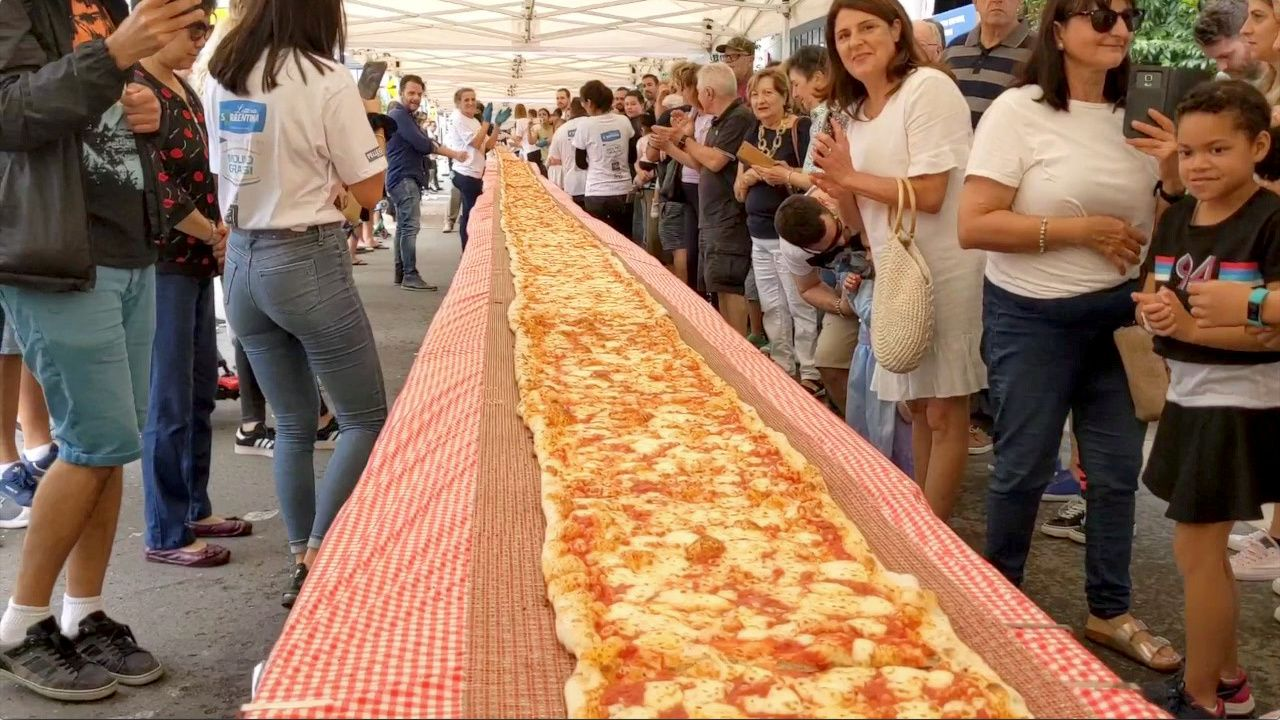 People look on as a 100m long margherita pizza sits on a table before receiving its final toppings, which was prepared by Pellegrini's Italian restaurant in their attempt to set a new record for Australia's longest pizza as part of a charity event to raise funds for the New South Wales Rural Fire Service, in Sydney, Australia, January 19, 2020, in this still image from video obtained via social media. Video taken January 19, 2020. INSTAGRAM/@ISSAC_EATSALOT via REUTERS ATTENTION EDITORS - THIS IMAGE HAS BEEN SUPPLIED BY A THIRD PARTY. MANDATORY CREDIT. NO RESALES. NO ARCHIVES.