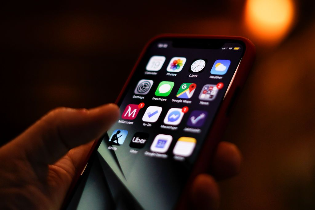The home screen of an Apple iPhone is seen displayed on a mobile device in front of a screen with data in this photo illustration in Warsaw, Poland on March 19, 2019. (Photo by Jaap Arriens/NurPhoto via Getty Images)