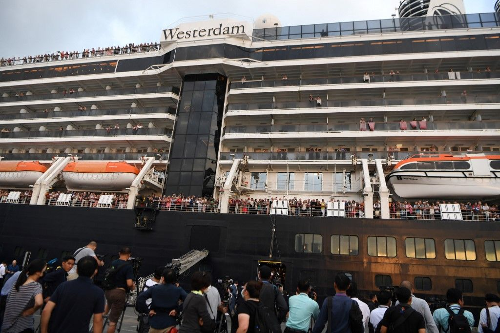 Passengers on board the Westerdam cruise ship look on in Sihanoukville on February 14, 2020, where the liner on February 13 docked after being refused entry at other Asian ports due to fears of the novel coronavirus. - Cambodia's strongman premier Hun Sen welcomed on February 14 the passengers of a US cruise ship blocked from several Asian ports over fears of a deadly new virus. (Photo by TANG CHHIN Sothy / AFP)
