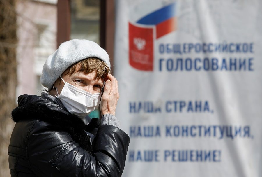 A woman wearing a protective mask, used as a measure to prevent the spread of coronavirus disease (COVID-19), stands at a public transport station near a board informing of a nationwide vote on constitutional changes in Stavropol, Russia March 26, 2020. REUTERS/Eduard Korniyenko