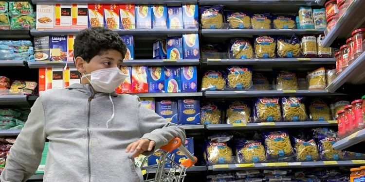 A boy wearing a protective face mask is seen at a market before the start of night-time curfew to contain the spread of the coronavirus disease (COVID-19) in Cairo, Egypt March 29, 2020. REUTERS/Amr Abdallah Dalsh