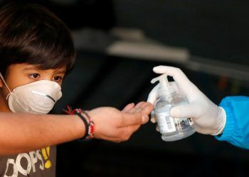 A child looks at the hand of his father while they wait to be checked by the medical team of NGO Intersos in a squatted building as the spread of coronavirus disease (COVID-19) continues, in Rome, Italy, April 3, 2020. REUTERS/Yara Nardi