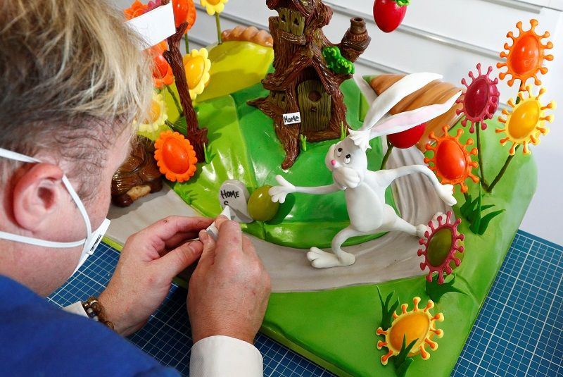 Belgian-based cake maker and pastry chef Michael Lewis-Anderson puts the finishing touches to a pastoral scene complete with chocolate tree and Easter eggs adorned with the spikes of the coronavirus in La Hulpe near Brussels, Belgium April 9, 2020. REUTERS/Francois Lenoir