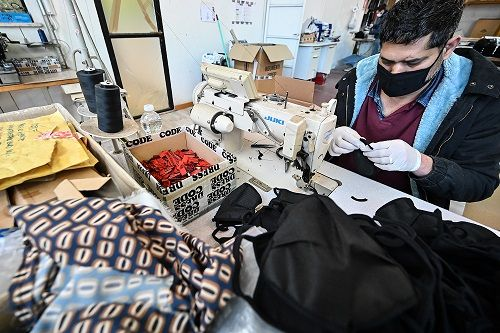 A worker sews Nonwoven fabric (TNT Tessuto non Tessuto) face masks, on Apri...</p></div><div class=