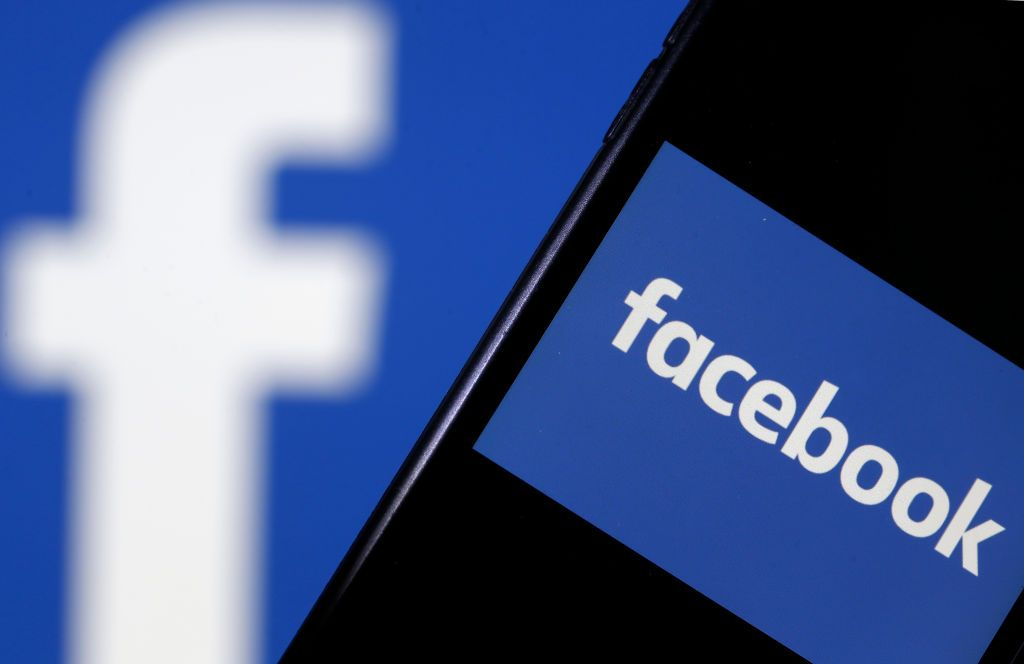 PARIS, FRANCE - SEPTEMBER 09: In this photo illustration, the Facebook logo is displayed on the screen of a smartphone in front of a computer screen displaying the logo of Facebook on September 09, 2019 in Paris, France. Several US states have launched antitrust investigations against web giants including Facebook and Google with the viewer their business practices, but also the collection and exploitation of personal data. In total, eight states have announced, via the attorneys general, the opening of an antitrust investigation against Facebook social media. (Photo by Chesnot/Getty Images)
