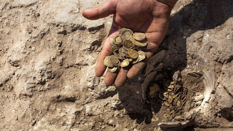 Israeli archaeologist Shahar Krispin shows gold coins, said by the Israel Antiquities Authority to date to the Abbasid dynasty, after its discovery at an archaeological site in Central Israel August 18, 2020. Picture taken August 18, 2020. Heidi Levine/Pool via REUTERS